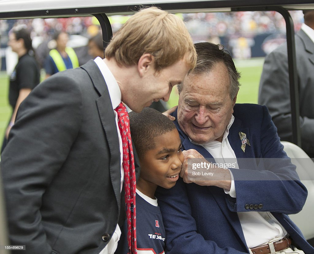 Former President George H.W. Bush on hand playfully gives a young man a fist to his face as his grandson Pierce Bush looks on at Salute To Service day before the Houston Texans play the Buffalo Bills at Reliant Stadium on November 4, 2012 in Houston, Texas.