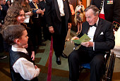 Former President George HW Bush talks with a young fan at The Points of Light Tribute at the Kennedy Center Washington DC March 21 2011
