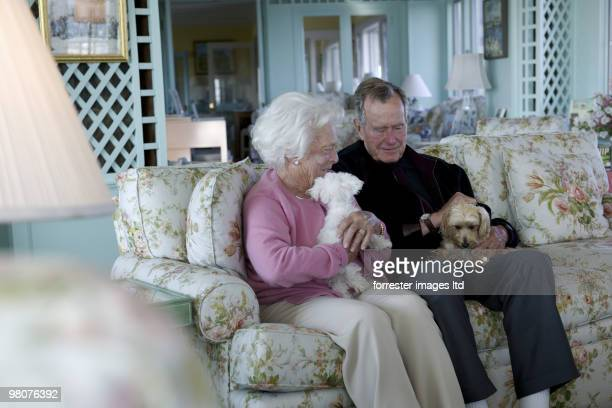 Former President George HW Bush with former First Lady Barbara Bush with their pet dogs during a portrait session for Parade Magazine at their home...