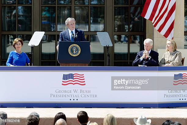Former President George W Bush delivers his speech as former first lady Laura Bush former President Bill Clinton and former first lady Hillary...