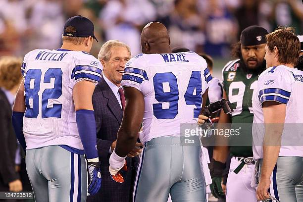 Former President George W Bush greets Jason Witten and DeMarcus Ware of the Dallas Cowboys as he was on hand for the opening coin toss against the...