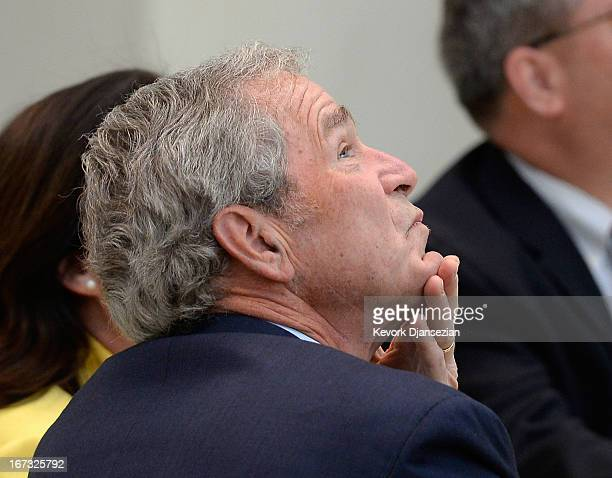 Former President George W Bush looks at the 360degree LED high definition video wall inside the Freedom Hall as he participates in a signing ceremony...