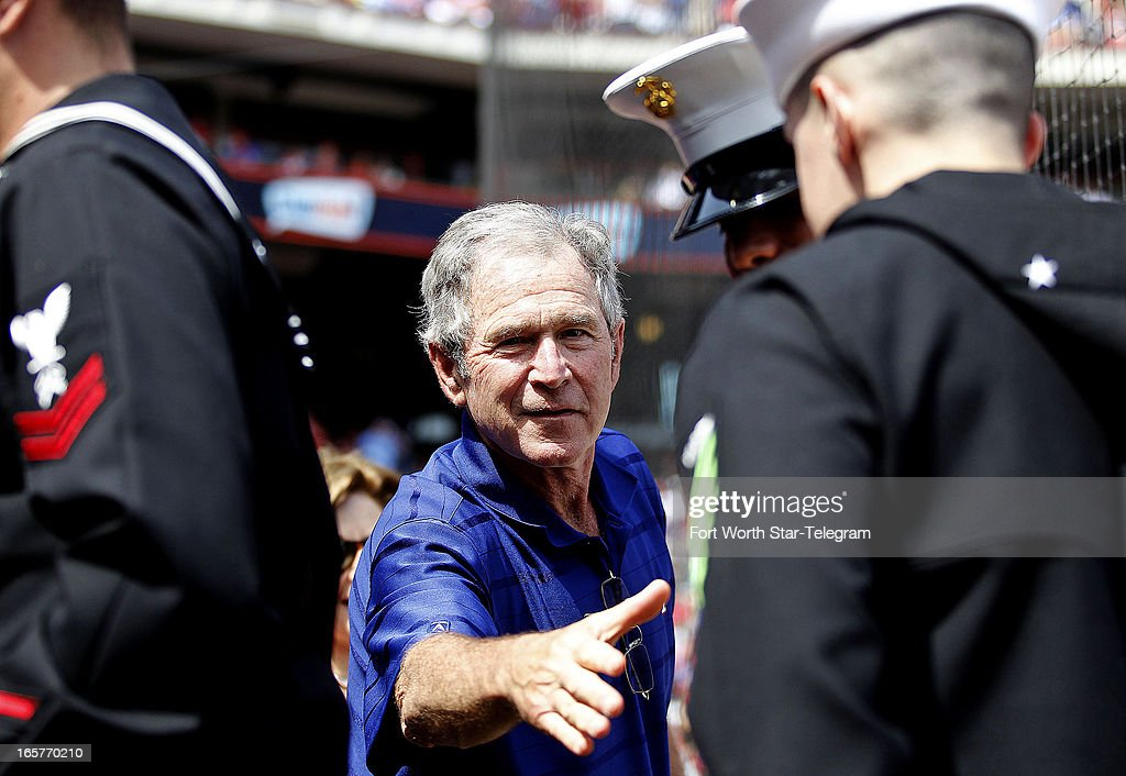 Former president George W. Bush shakes the hands of servicemen during the game between the Texas Rangers and Los Angeles Angels at Rangers Ballpark in Arlington, Texas, Friday, April 5, 2013. The Rangers defeated the Angels 3-2.