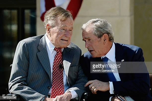 Former President George W Bush talks to his father President George HW Bush during the opening ceremony of the George W Bush Presidential Center...