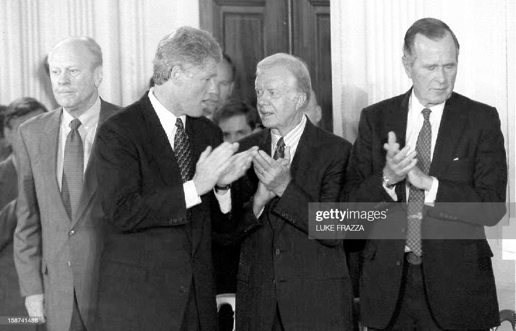Former President Gerald Ford, U.S. President Bill Clinton, Former President Jimmy Carter and Former President George Bush applaud after the signing of side agreements to the North American Free Trade Agreement 14 September 1993 at the White House in Washington, D.C. The former president added their support to the passing of the main NAFTA agreement.
