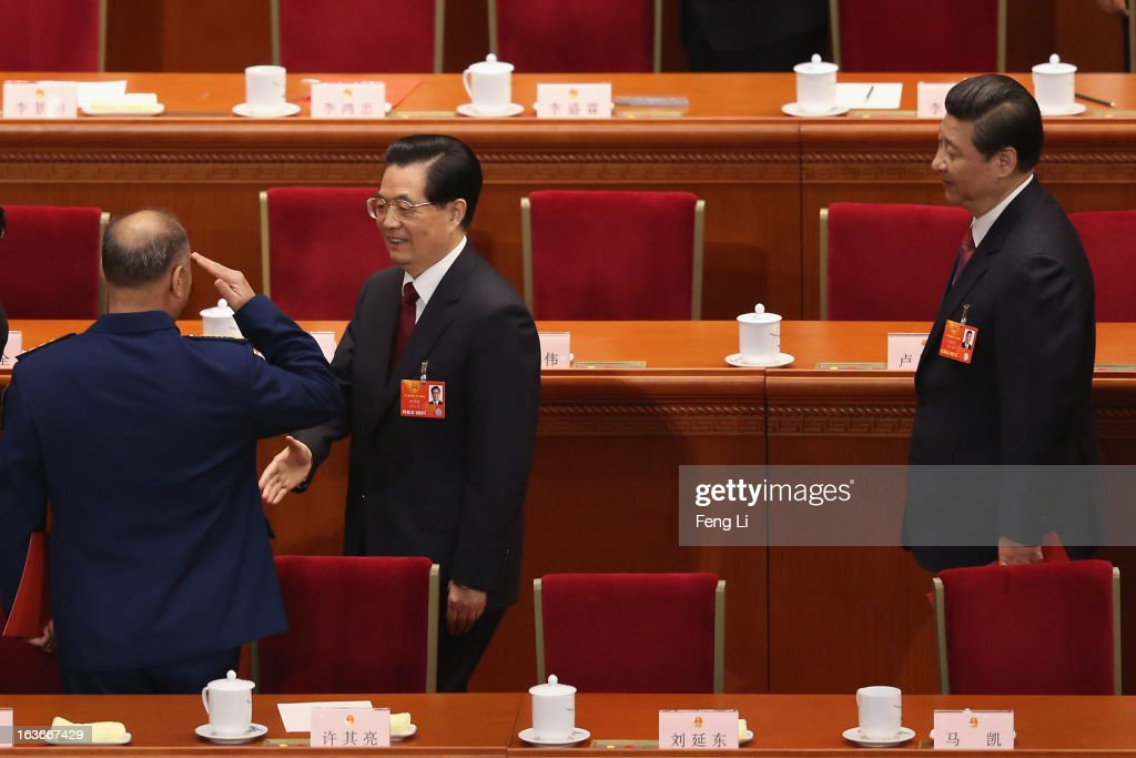 Former President Hu Jintao (C) shakes hands with Chinese vice chairman of the Central Military Commission Xu Qiliang (L) as newly-elected Chinese President Xi Jinping (R) following after the fourth plenary meeting of the National People's Congress (NPC) at the Great Hall of the People on March 14, 2013 in Beijing, China. Xi Jinping, general secretary of the Communist Party of China Central Committee, was elected President of the People's Republic of China and Chairman of the Central Military Commission on Thursday.