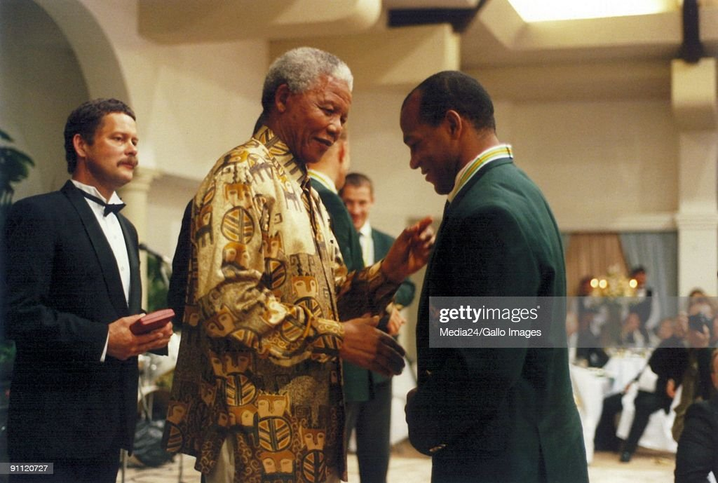 Former President Nelson Mandela shakes the hand of Springbok player, Chester Williams.