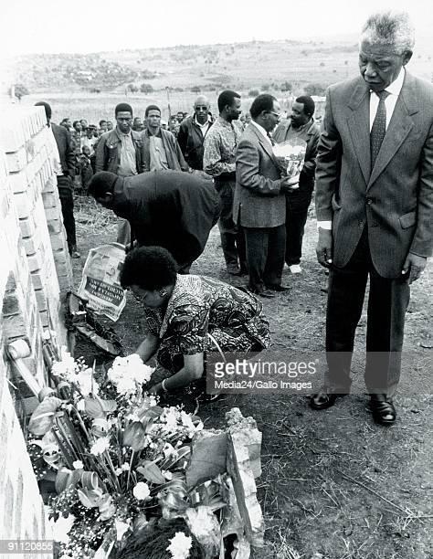 Former President Nelson Mandela watches as Graca Machel puts flowers on her deceased husband Samora Machel's tombstone