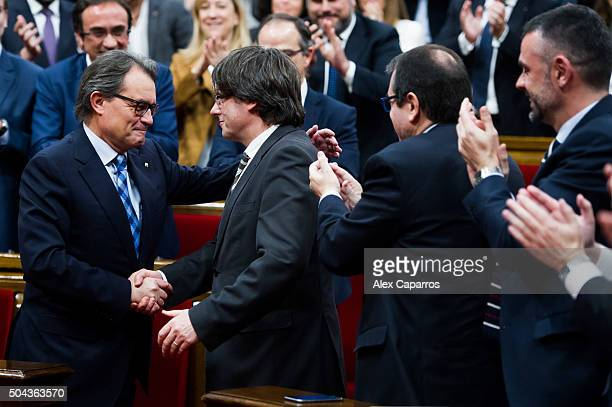 Former President of Catalonia Artur Mas congratulates Carles Puigdemont after he was elected new President of Catalonia during the parliamentary...