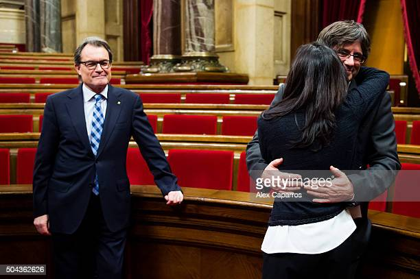 Former President of Catalonia Artur Mas looks on as the new President of Catalonia Carles Puigdemont embraces his wife Marcela Topor after the...
