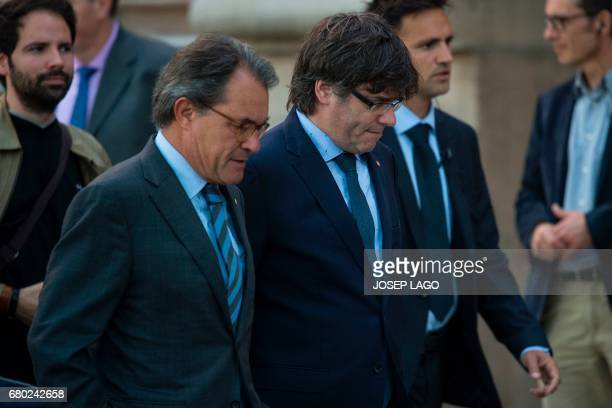 Former President of the Catalan Government Artur Mas and President of the Catalan Government Carles Puigdemont leave after accompanying Catalan...