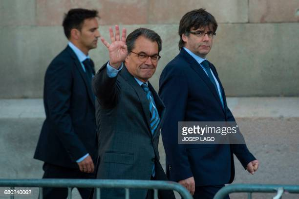 Former President of the Catalan Government Artur Mas waves past President of the Catalan Government Carles Puigdemont as they leave after...