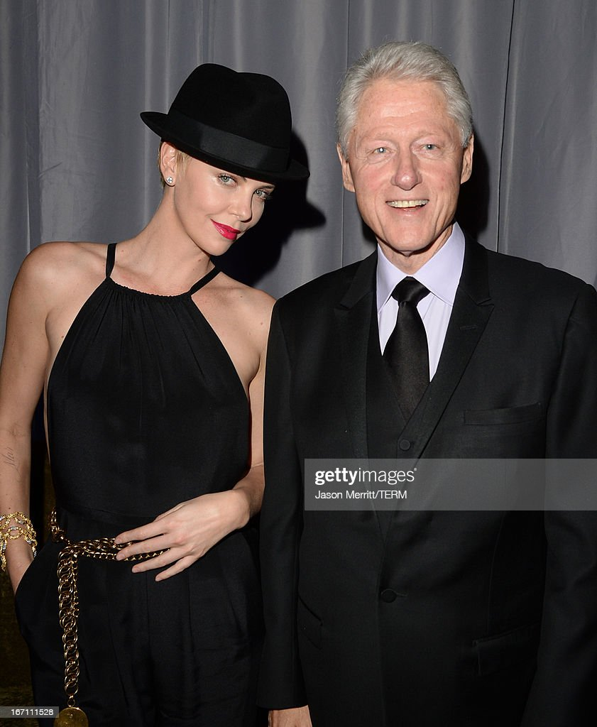 Former President of the United States Bill Clinton (R) gives actress Charlize Theron his hat backstage during the 24th Annual GLAAD Media Awards at JW Marriott Los Angeles at L.A. LIVE on April 20, 2013 in Los Angeles, California.