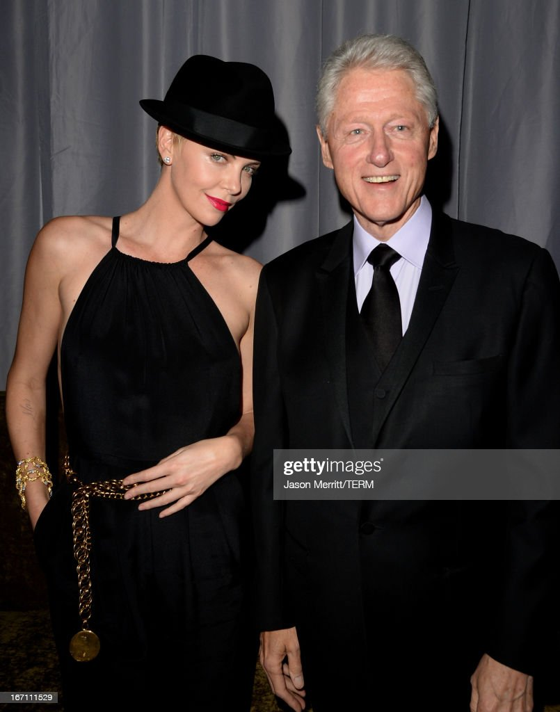 Former President of the United States <a gi-track='captionPersonalityLinkClicked' href=/galleries/search?phrase=Bill+Clinton&family=editorial&specificpeople=67203 ng-click='$event.stopPropagation()'>Bill Clinton</a> (R) gives actress <a gi-track='captionPersonalityLinkClicked' href=/galleries/search?phrase=Charlize+Theron&family=editorial&specificpeople=171250 ng-click='$event.stopPropagation()'>Charlize Theron</a> his hat backstage during the 24th Annual GLAAD Media Awards at JW Marriott Los Angeles at L.A. LIVE on April 20, 2013 in Los Angeles, California.