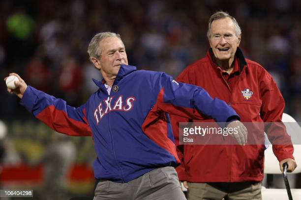 Former President of the United States George W Bush throws out the first pitch as his father Former President George HW Bush looks on before the...