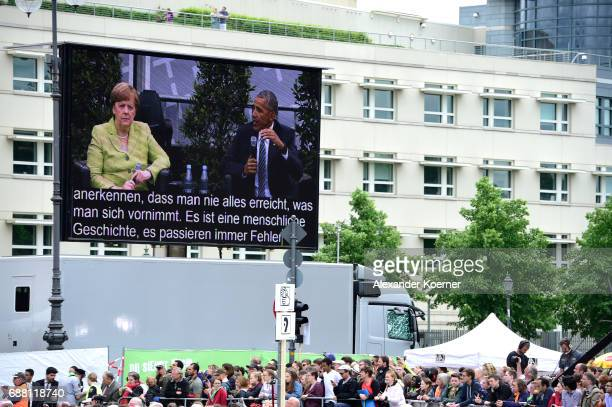 Former President of the United States of America Barack Obama and German chancellor Angela Merkel are seen on a large screen while speaking on stage...