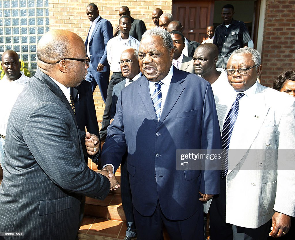 Former president Rupiah Banda talks to MMD party president Nevers Mumba on April 17 2013 at the Lusaka Magistrate Court as he faces charges of abuse...
