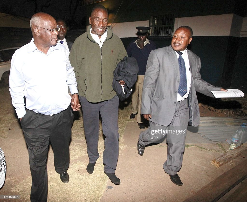 Former President Rupiah Banda's son Andrew is escorted by criminal investigation officers as he is released from police cells at Woodlands police...