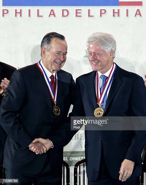 Former presidents George HW Bush and Bill Clinton shake hands after they received the 2006 Liberty Medal October 5 2006 in Philadelphia Pennsylvania...