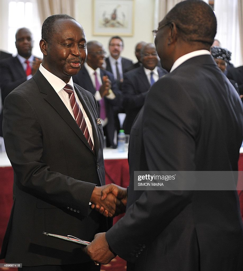 Former presidents of the Central African Republic Michel Djotodia (R) and François Bozize (background) shake hands, on April 14, 2015 in Nairobi, after signing a ceasefire deal after months of negotiations mediated by Kenya. AFP PHOTO/SIMON MAINA