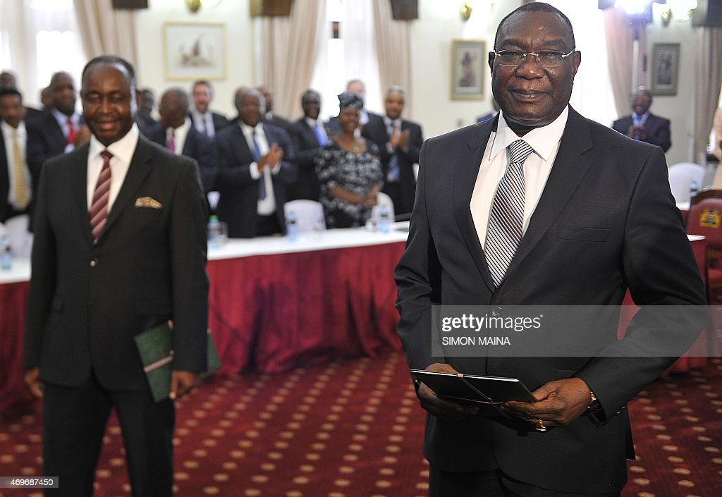 Former presidents of the Central African Republic Michel Djotodia (R) and François Bozize (background) are applauded, on April 14, 2015 in Nairobi, after signing a ceasefire deal after months of negotiations mediated by Kenya. AFP PHOTO/SIMON MAINA