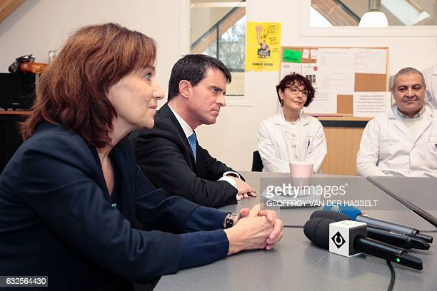 Former prime minister and candidate for the leftwing primaries Manuel Valls talks with workers and volunteers next to French Minister for Family...