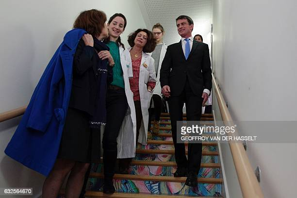 Former prime minister and candidate for the leftwing primaries Manuel Valls smiles next to French Minister for Family Children and Women's Rights...