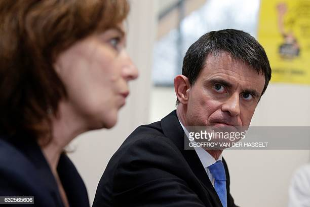 Former prime minister and candidate for the leftwing primaries Manuel Valls looks on next to French Minister for Family Children and Women's Rights...