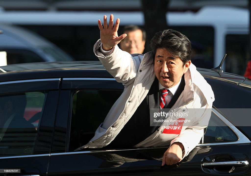 Former Prime Minister and leader of Japan's main opposition Liberal Democratic Party (LDP) <a gi-track='captionPersonalityLinkClicked' href=/galleries/search?phrase=Shinzo+Abe&family=editorial&specificpeople=559017 ng-click='$event.stopPropagation()'>Shinzo Abe</a> waves to supporters from his car during an election campaign on December 13, 2012 in Osaka, Japan. Japanese voters will go to the polls for a general election on December 16, 2012.