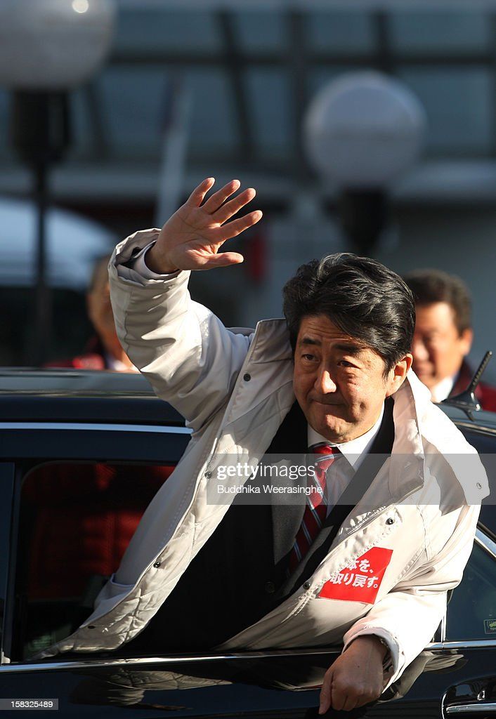 Former Prime Minister and leader of Japan's main opposition Liberal Democratic Party (LDP) <a gi-track='captionPersonalityLinkClicked' href=/galleries/search?phrase=Shinzo+Abe&family=editorial&specificpeople=559017 ng-click='$event.stopPropagation()'>Shinzo Abe</a> waves to supporters from his car during an election campaign on December 13, 2012 in Osaka, Japan. Japanese voters will go to the polls for a general election on December 16.