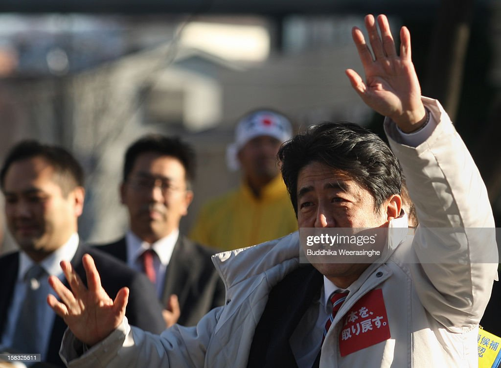 Former Prime Minister and leader of Japan's main opposition Liberal Democratic Party (LDP) <a gi-track='captionPersonalityLinkClicked' href=/galleries/search?phrase=Shinzo+Abe&family=editorial&specificpeople=559017 ng-click='$event.stopPropagation()'>Shinzo Abe</a>(R) waves to supporters during his party election campaign on December 13, 2012 in Osaka, Japan. Japanese voters will go to the polls for a general election on December 16, 2012.