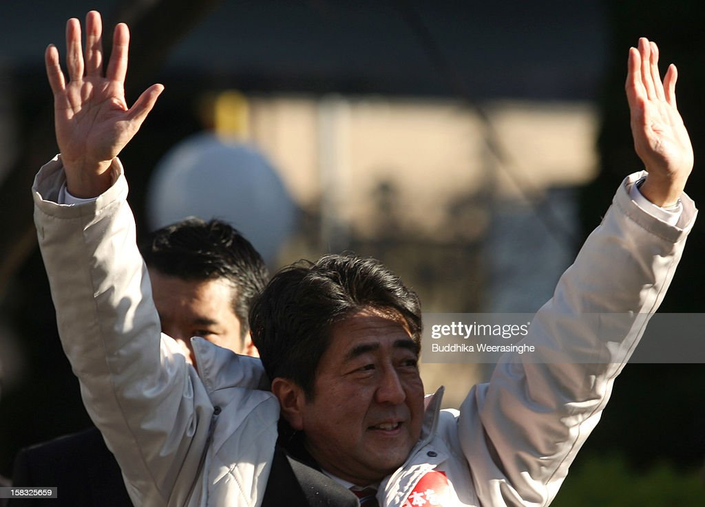 Former Prime Minister and leader of Japan's main opposition Liberal Democratic Party (LDP) <a gi-track='captionPersonalityLinkClicked' href=/galleries/search?phrase=Shinzo+Abe&family=editorial&specificpeople=559017 ng-click='$event.stopPropagation()'>Shinzo Abe</a> waves to supporters during his party election campaign on December 13, 2012 in Osaka, Japan. Japanese voters will go to the polls for a general election on December 16.