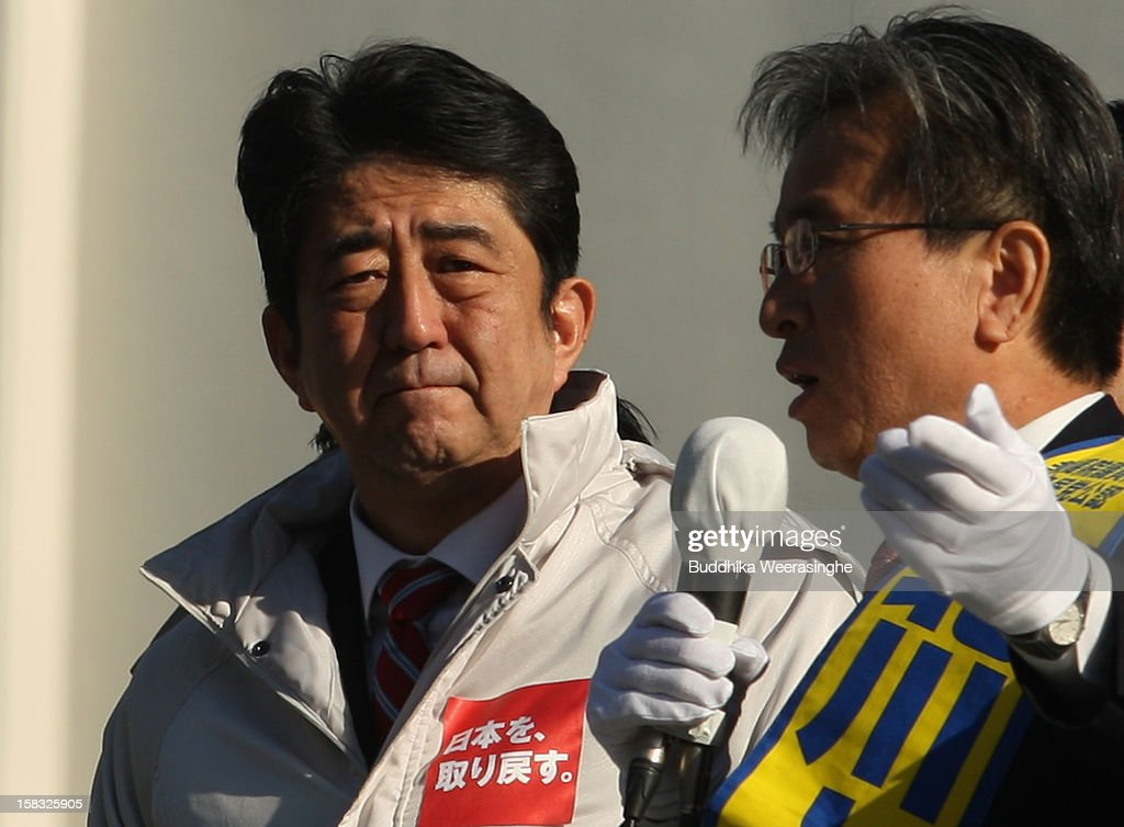 Former Prime Minister and leader of Japan's main opposition Liberal Democratic Party (LDP) <a gi-track='captionPersonalityLinkClicked' href=/galleries/search?phrase=Shinzo+Abe&family=editorial&specificpeople=559017 ng-click='$event.stopPropagation()'>Shinzo Abe</a> (L) listens to LDP candidate Kitagawa Tomokatsu's speech, which was made from the roof of the campaign car during party election campaign on December 13, 2012 in Osaka, Japan. Japanese voters will go to the polls for a general election on December 16.