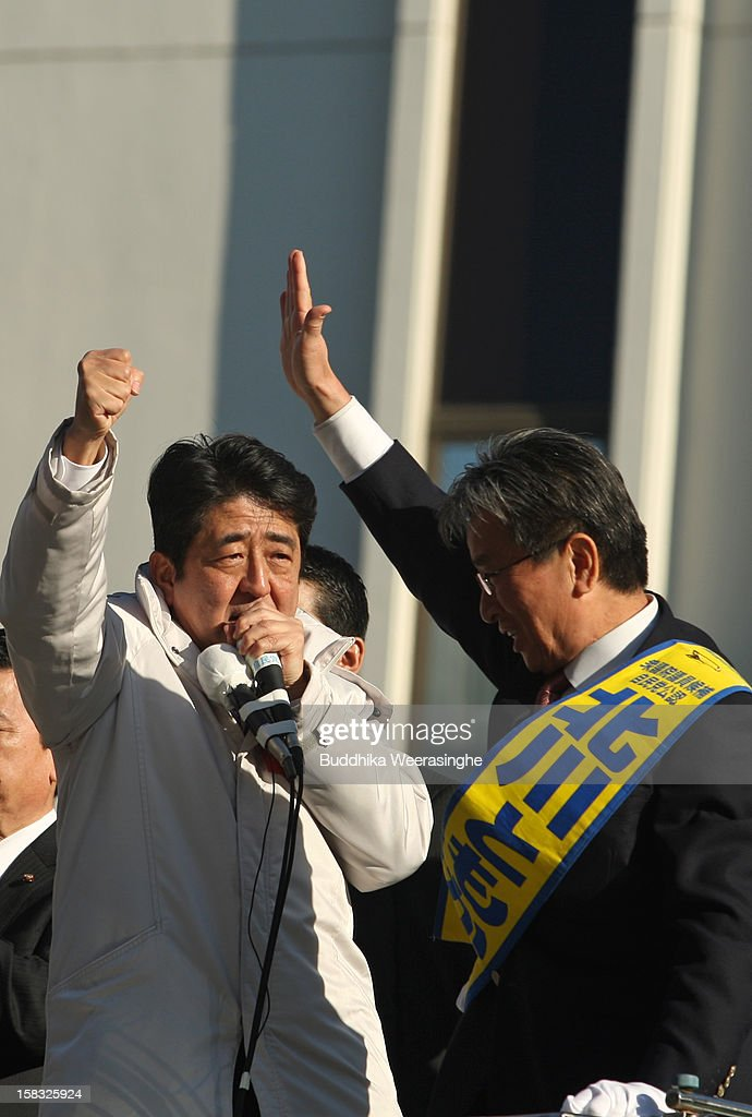 Former Prime Minister and leader of Japan's main opposition Liberal Democratic Party (LDP) <a gi-track='captionPersonalityLinkClicked' href=/galleries/search?phrase=Shinzo+Abe&family=editorial&specificpeople=559017 ng-click='$event.stopPropagation()'>Shinzo Abe</a> (L) and LDP candidate Kitagawa Tomokatsu wave to supporters from the roof of the campaign car during their party election campaign on December 13, 2012 in Osaka, Japan. Japanese voters will go to the polls for a general election on December 16.