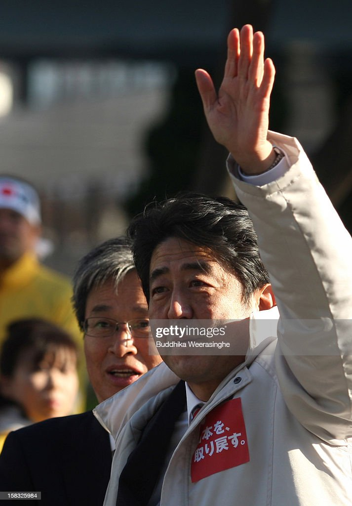 Former Prime Minister and leader of Japan's main opposition Liberal Democratic Party (LDP) Shinzo Abe (R) waves to suppoters as LDP candidate Kitagawa Tomokatsu looks on during their party election campaign on December 13, 2012 in Osaka, Japan. Japanese voters will go to the polls for a general election on December 16.