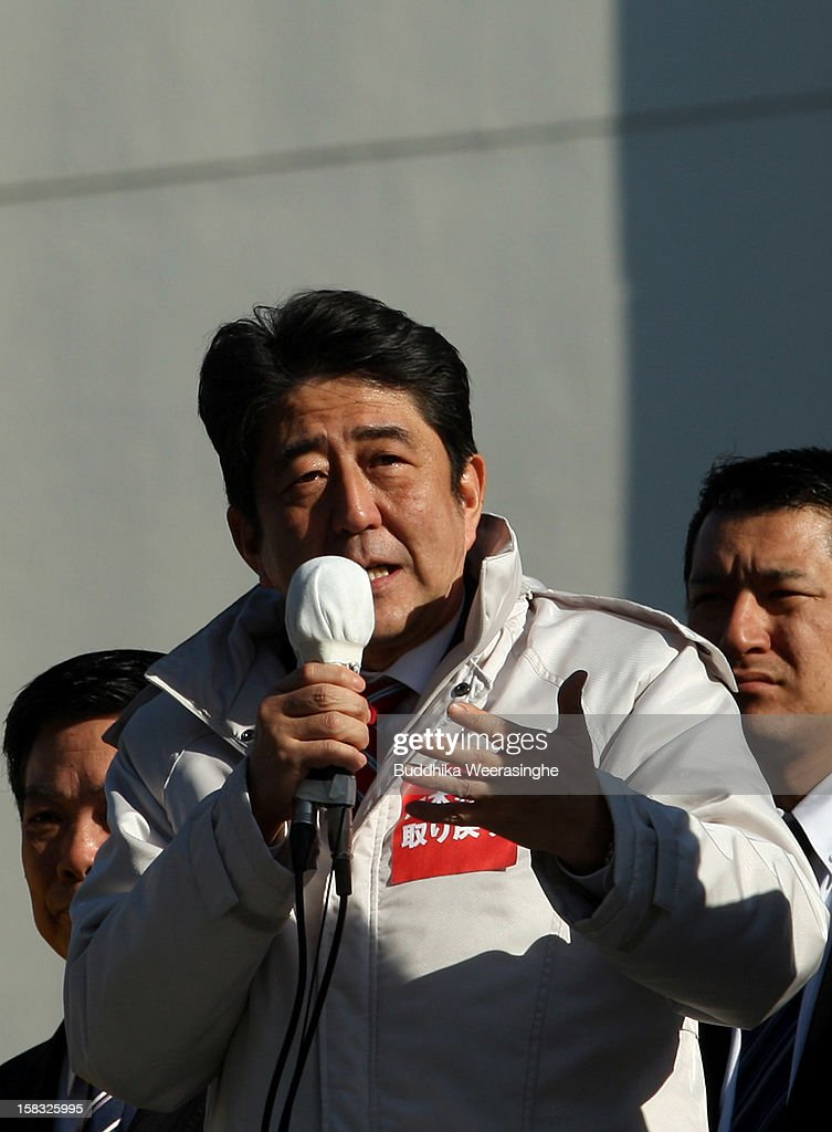 Former Prime Minister and leader of Japan's main opposition Liberal Democratic Party (LDP) <a gi-track='captionPersonalityLinkClicked' href=/galleries/search?phrase=Shinzo+Abe&family=editorial&specificpeople=559017 ng-click='$event.stopPropagation()'>Shinzo Abe</a> gives a speech from the roof of a campaign car during his party election campaign on December 13, 2012 in Osaka, Japan. Japanese voters will go to the polls for a general election on December 16.