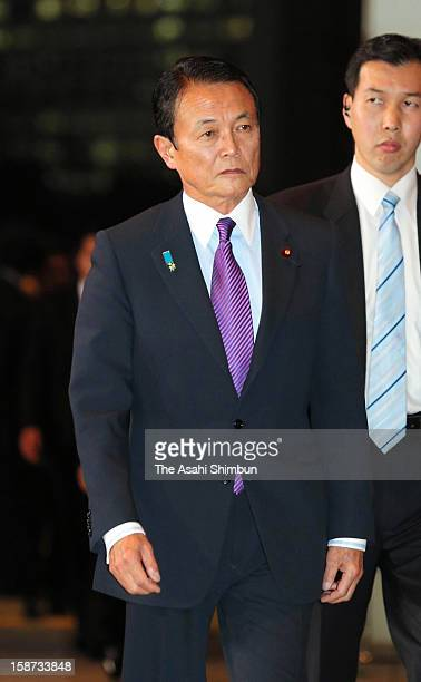 Former Prime Minister and newly appointed deputy Prime Minister and Finance Minister Taro Aso enters Japan's new Prime Minister Shinzo Abe's official...