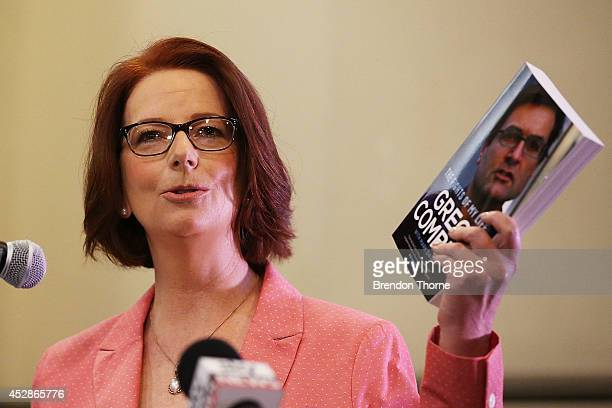 Former Prime Minister Julia Gillard holds Greg Combet's book aloft at the launch of former cabinet minister Greg Combet's book 'The Fights of My...