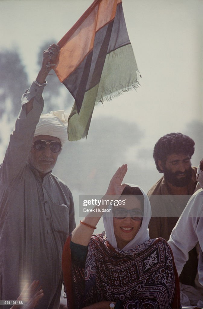 Former Prime Minister of Pakistan, Benazir Bhutto (1953 - 2007) campaigning for the Pakistan Peoples Party (PPP) in the week before the Pakistani General Election, Pakistan, 15-16th October 1990. Behind her, a supporter waves the colours of the PPP.