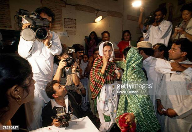 Former prime minister of Pakistan Benazir Bhutto pictured surrounded by the press when voting in Islamabad Pakistan in 1991