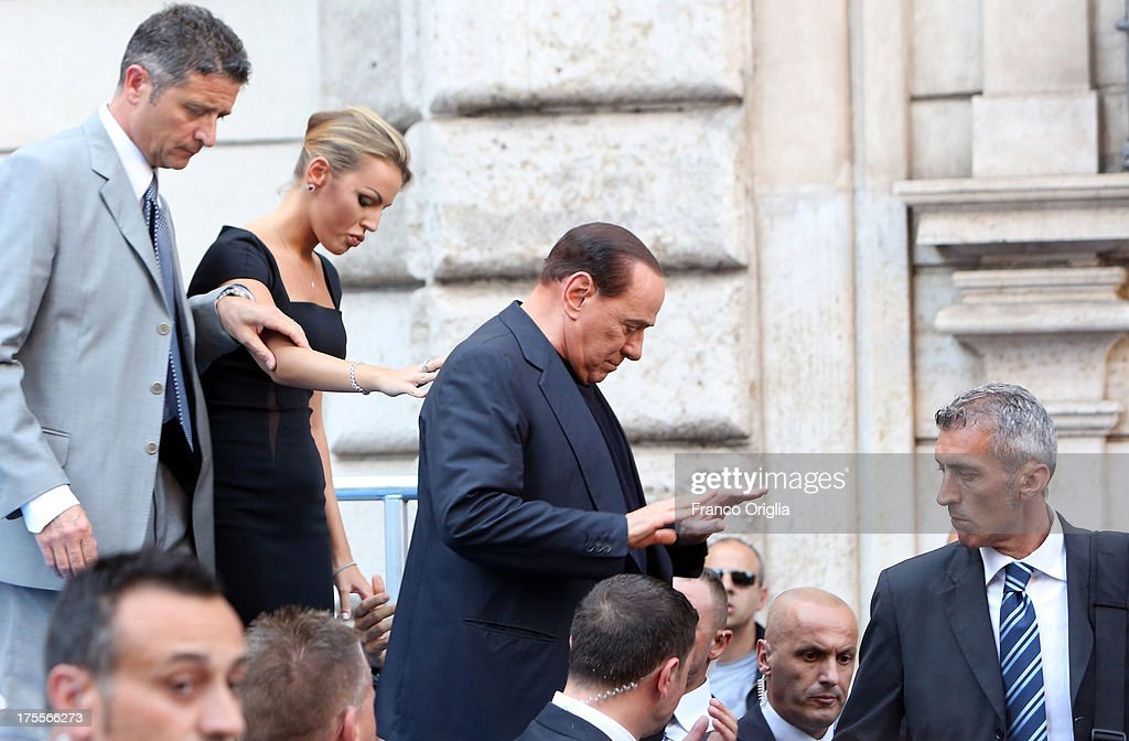 Former Prime Minister Silvio Berlusconi flanked by his girlfriend <a gi-track='captionPersonalityLinkClicked' href=/galleries/search?phrase=Francesca+Pascale&family=editorial&specificpeople=10015825 ng-click='$event.stopPropagation()'>Francesca Pascale</a> leaves the stage after speaking to supporters during a Pro-Berlusconi rally outside his Rome residence, Palazzo Grazioli at Via del Plebiscito, on August 4, 2013 in Rome, Italy. Italy's Supreme court has rejected Berlusconi's final appeal against a conviction for tax fraud, upholding a four-year prison sentence for the former leader.