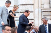 Former Prime Minister Silvio Berlusconi flanked by his girlfriend Francesca Pascale leaves the stage after speaking to supporters during a...