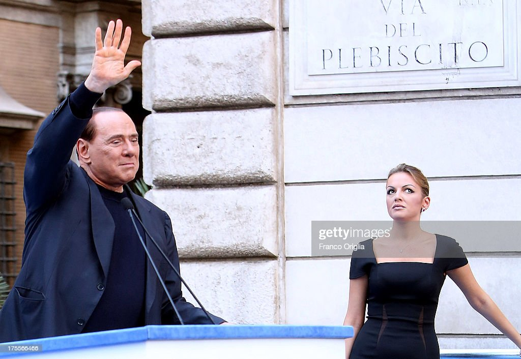 Former Prime Minister <a gi-track='captionPersonalityLinkClicked' href=/galleries/search?phrase=Silvio+Berlusconi&family=editorial&specificpeople=201842 ng-click='$event.stopPropagation()'>Silvio Berlusconi</a>, flanked by his new girlfriend <a gi-track='captionPersonalityLinkClicked' href=/galleries/search?phrase=Francesca+Pascale&family=editorial&specificpeople=10015825 ng-click='$event.stopPropagation()'>Francesca Pascale</a>, waves to his supporters during a Pro-Berlusconi rally outside his Rome residence, Palazzo Grazioli at Via del Plebiscito, on August 4, 2013 in Rome, Italy. Italy's Supreme court has rejected Berlusconi's final appeal against a conviction for tax fraud, upholding a four-year prison sentence for the former leader.
