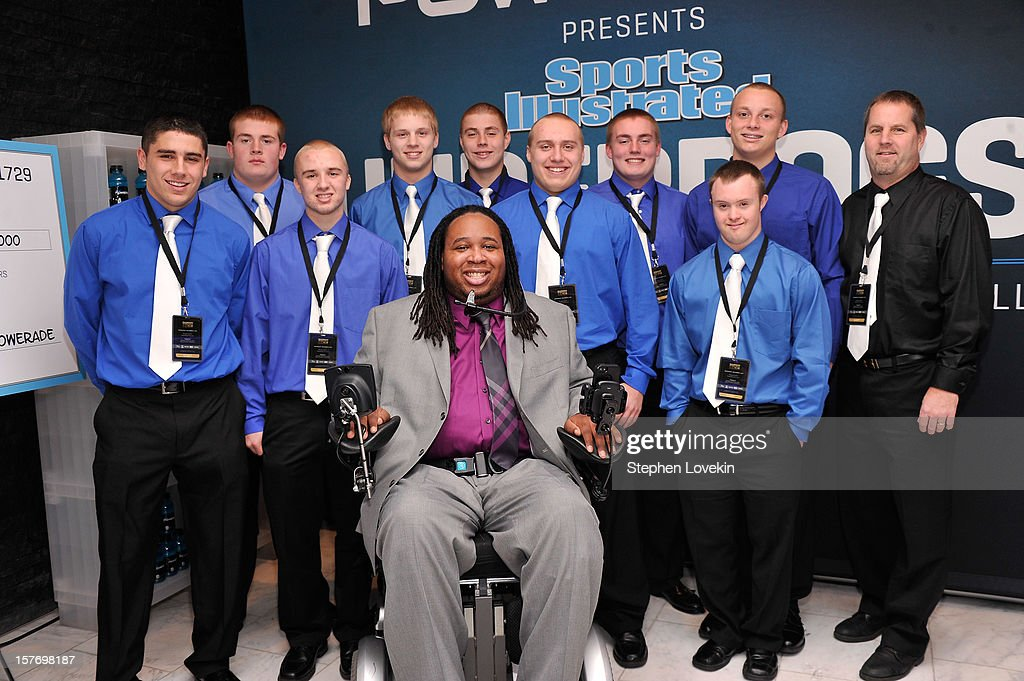 Former professional football player Eric LeGrand (C) poses with Ishpeming Football Coach Jeff Olson (R), kicker Eric Dompierre (2nd R), and the Ishpeming High School football team at the 2012 Sports Illustrated Sportsman of the Year award presentation at Espace on December 5, 2012 in New York City.
