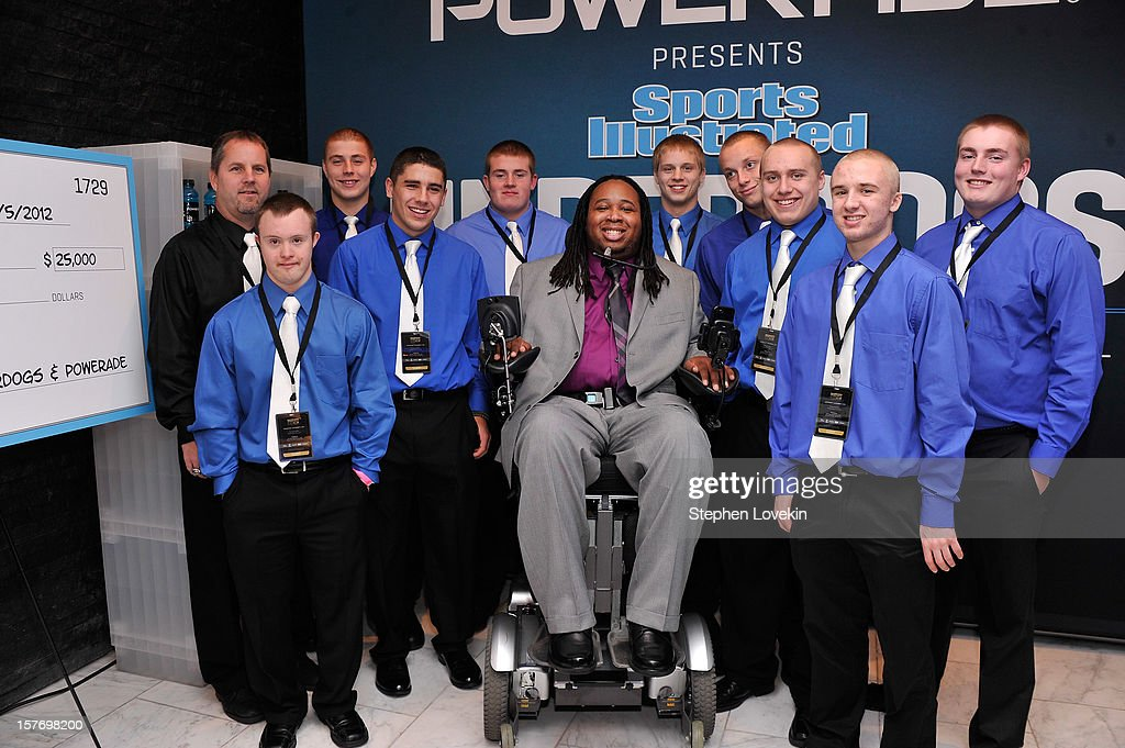 Former professional football player Eric LeGrand (C) poses with Ishpeming Football Coach Jeff Olson (L), kicker Eric Dompierre (2nd L), and the Ishpeming High School football team at the 2012 Sports Illustrated Sportsman of the Year award presentation at Espace on December 5, 2012 in New York City.