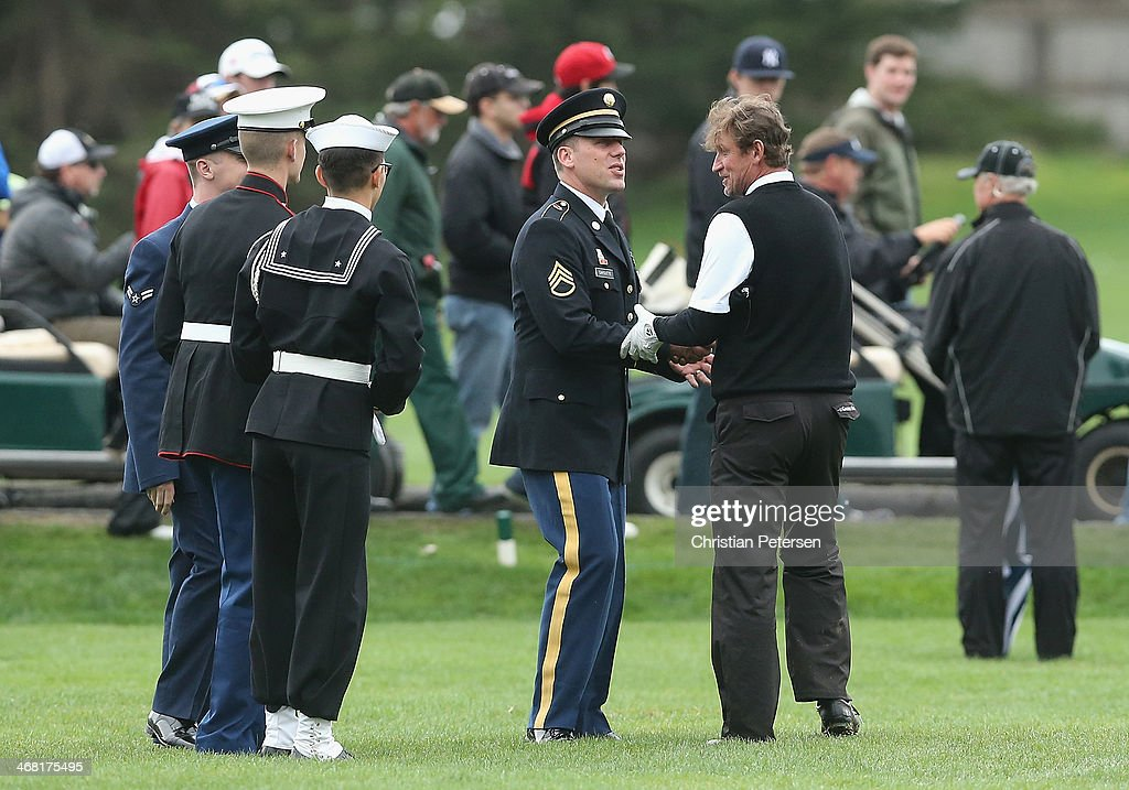 Former professional hockey player shakes the hand of a military service man during the final round of the AT&T Pebble Beach National Pro-Am at the Pebble Beach Golf Links on February 9, 2014 in Pebble Beach, California.