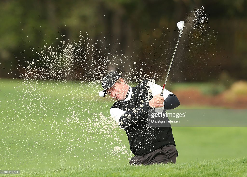 Former professional hockey player Wayne Gretzky hits out of a bunker and onto the second hole green during the final round of the AT&T Pebble Beach National Pro-Am at the Pebble Beach Golf Links on February 9, 2014 in Pebble Beach, California.
