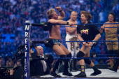 Former professional wrestlers Ric Flair looks on as WWE Superstar Chris Jericho gets pummeled on the ropes by 'Rowdy' Roddy Piper Ricky 'The Dragon'...
