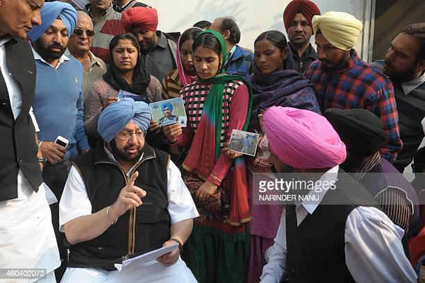 Former Punjab Chief Minister and member of parliament from Amritsar Amarinder Singh talks with relatives of Indian workers who were taken hostage in...