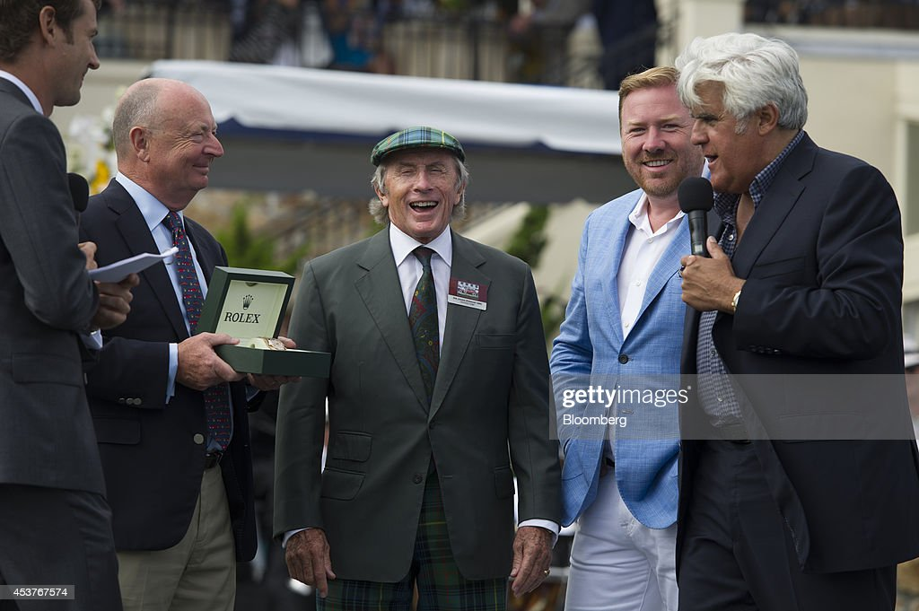 Former race car driver <a gi-track='captionPersonalityLinkClicked' href=/galleries/search?phrase=Jackie+Stewart+-+Race+Car+Driver&family=editorial&specificpeople=167276 ng-click='$event.stopPropagation()'>Jackie Stewart</a>, center, laughs as entertainer <a gi-track='captionPersonalityLinkClicked' href=/galleries/search?phrase=Jay+Leno+-+Television+Host&family=editorial&specificpeople=156431 ng-click='$event.stopPropagation()'>Jay Leno</a>, right, speaks during the 2014 Pebble Beach Concours d'Elegance in Pebble Beach, California, U.S., on Sunday, Aug. 17, 2014. The annual event, now in its 64th year, raised a record $301.9 million in 2013, the highest total for a series of classic car auctions anywhere in the world. Photographer: David Paul Morris/Bloomberg via Getty Images